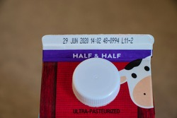 Half and half with expiration date on the container. Cream for coffee.