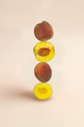 Half and whole peach fruit balancing on the table.