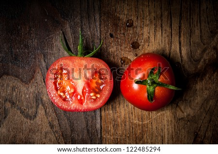 half and whole tomatoes on brown textured wood
