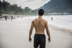 Half body back shot of a handsome young man standing on a beach in Phuket Island, Thailand, shirtless wearing boxer shorts, showing muscular fit body