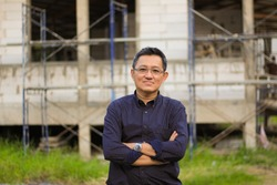 half body portrait of an asian man in crossed arms position with construction site as a background