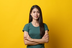 Half body shot beauty asian confidence teenager in green tee shirt folded arms and smiling stand isolated on yellow background in studio.