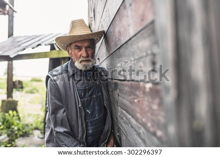 Half Body Shot of a Middle Aged Bearded Male Farmer Wearing Straw Hat and Jacket, Leaning Against Wall of Farmhouse and Looking Straight at the Camera.