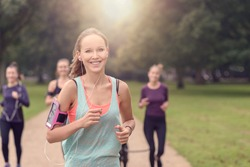 Half Body Shot of an Athletic Pretty Young Woman Smiling at the Camera While Jogging at the Park with Other Girls, with copy space on the right