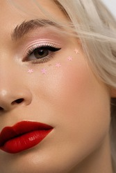 Half close-up portrait of a woman with shiny clean skin and curly blond hair. Rhinestones stars on the eyes, evening makeup and red lipstick. soft care, full lips, long eyelashes and thick eyebrows