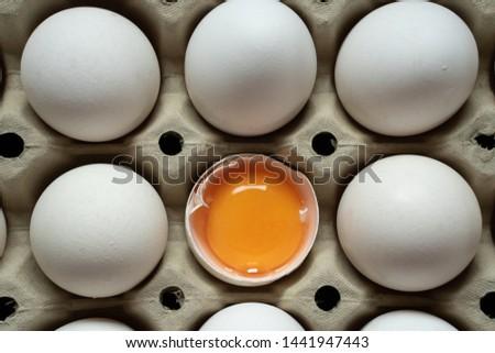 Half cracked egg in the paper egg tray. Egg yolk in egg shell. White eggs #1441947443