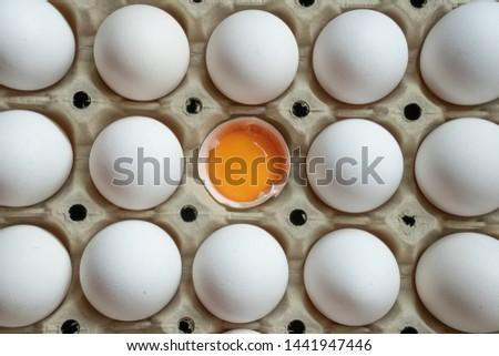 Half cracked egg in the paper egg tray. Egg yolk in egg shell. White eggs #1441947446