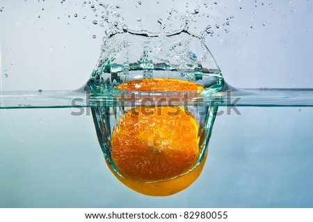 half cut orange drop into water with splash
