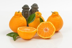 Half cut Tangerines Hallabong with two black Dolhareubangs on white background, South Korea. It is a cultivar of citrus fruits bred in Japan in 1972