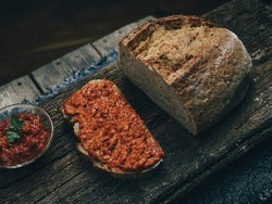Half-cutted whole grain, rye bread on a wooden surface. Slice of bread with balkan traditional spread on it. Bakery product decorated with ajvar.
