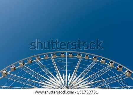 Half Cycle of White Ferris wheel and blue sky