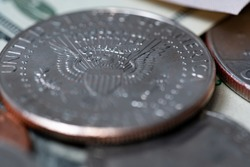 Half dollar coin closeup. Eagle on the half dollar Kennedy coin. Dollar banknotes in the background