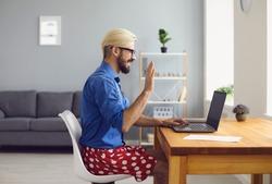 Half dressed employee guy greeting online colleague in living room.
