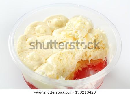 Half-eaten strawberry shortcake dessert in plastic cup