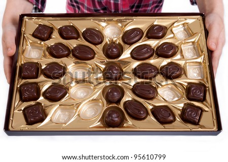 half empty box of chocolates in little girl hands