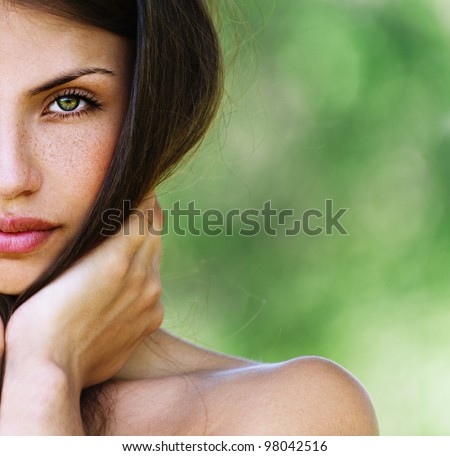 half face beautiful sexy girl with bare shoulders seductively posing with his hands touching face