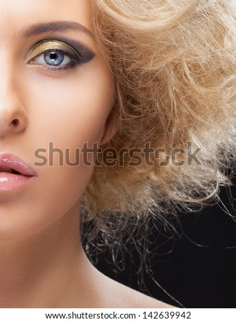 Half face closeup portrait of beautiful blond girl with golden eyeshadows and fluffy hair
