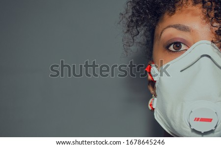 Half face of a black woman wearing a FFP3 mask with exhalation valve during Coronavirus crisis.  Copy space.