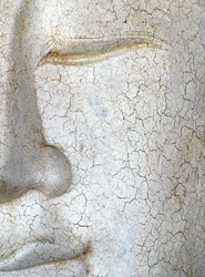 Half face of a peaceful white cracked Buddha statue face with eyes closed