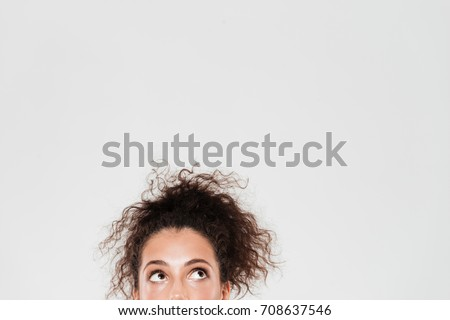 Half face of pretty curly woman looking up over gray background