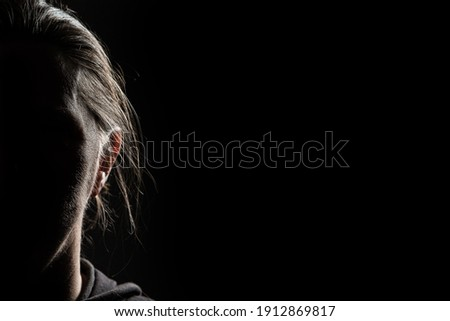 Half face of unrecognizable woman in shadow shrouded in darkness isolated on black background with wide copy space, concept of anonymity to hide one's identity, women who have suffered violence Сток-фото ©