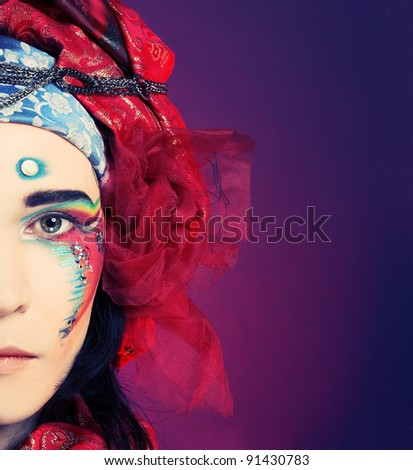 Half face of young man in creative eastern image in red turban and with artistic make-up