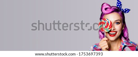 Half face portrait of excited surprised woman with lollipop covering eye. Pin up girl with happy opened mouth. Purple model at retro concept. Grey color background. Wide composition with copy space.