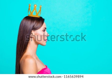 Half faced turned close up studio photo portrait of pretty attractive confident charming cute lovely serious lady wearing crown on head isolated on bright vivid blue background