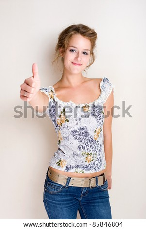Half figure portrait of a cheerful fashionable young blond woman showing thumbs up.
