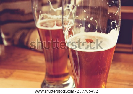 Photo of Half-full glasses of beer toned image. Glasses of beer on wooden table. Side view creative toned photo of man sitting at wooden table part view. There is free space in the left of table.