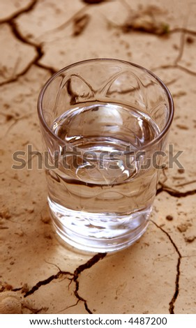 half glass of water on cracked earth