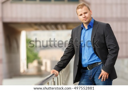 half growth portrait of handsome young businessman in black jacket, jeans and blue shirt walking outdoors #497552881