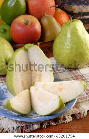 Half guava and slices with the complete one on table