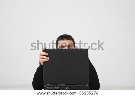Half head of a hacker man behind a laptop