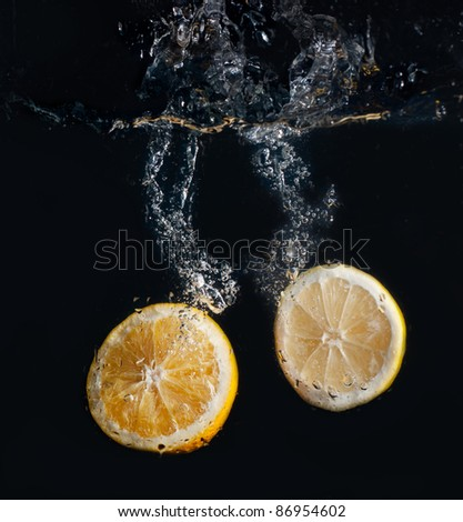 Half lemon and orange falling into water on black background