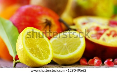 Half Lemon slices and berry of pomegranate - stock photo