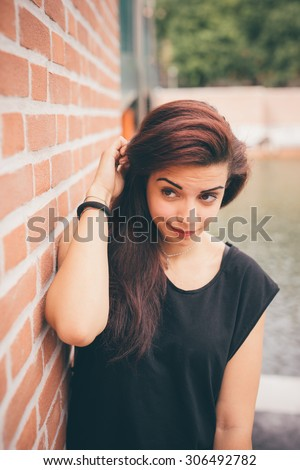 Half length of a young beautiful reddish brown hair caucasian girl posing leaning against a wall looking in camera - carefreeness, freshness, youth concept - dressed blue jeans and black shirt