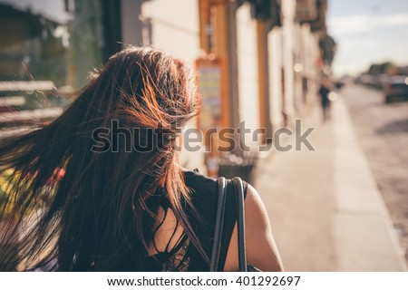 Half length of a young reddish brown hair caucasian woman viewed from back walking in the city back light - youth, freshness, carefree concept