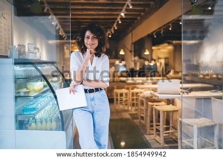 Half length of cheerful Caucaisan entrepreneur feeling success in franchise coffee shop standing in doorway and smiling at camera, happy self employed woman working in local cafeteria industry Stockfoto ©