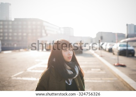 Half length of young beautiful asian long brown straight hair hipster woman, overlooking left, pensive, in the city during sunset in backlight- thoughtful, thinking future concept