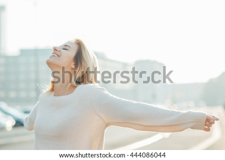 Half length of young beautiful cacuasian woman feeling free with arms wide open in the city back light - liberty, freedom, girl power concept