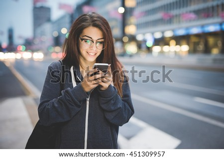 Half length of young beautiful caucasian brown hair woman with glasses tapping the screen of a smart phone hand hold in the city evening - technology, social network, communication concept #451309957
