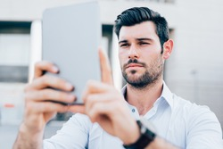 Half length of young handsome caucasian black hair modern businessman using a tablet taking photos - technology, social network concept