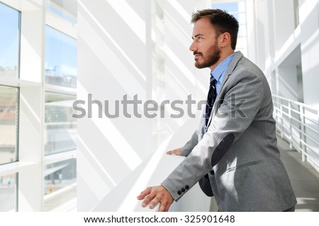 Half length portrait of a men dressed in luxury elegant clothes watching in window while standing in modern space, thoughtful successful businessman in suit resting after meeting with his partners