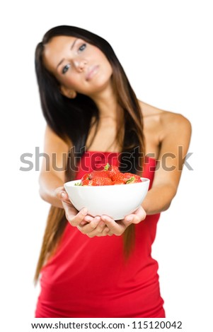 Half length portrait of a slender young brunette holding bowl of strawberries.