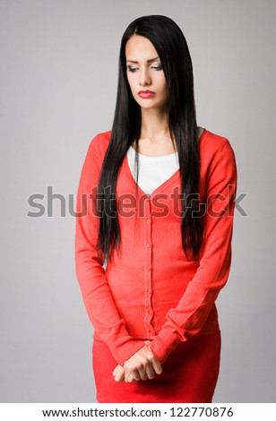 Half length portrait of attractive slender young business woman in pensive pose.