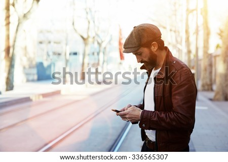 Half length portrait of bearded hipster man dressed in stylish clothes chatting on cell telephone while standing in the street, glamorous male with cool style use smart phone during strolling outdoors