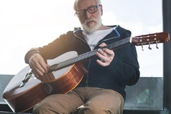 Half-length portrait of calm old man playing favorite song at home. He is thoughtfully touching strings of guitar while sitting at window