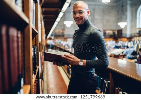 Half length portrait of caucasian cheerful successful adult student in eyewear standing with book in the school library archive room, many tomes of ancient textbooks on shelves in publicity area