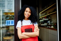 Half length portrait of cheerful african american professional barista in red apron smiling at camera.Positive dark skinned female waitress with crossed hands standing at entrance to own coffee shop